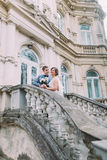 Cheerful just married couple in love posing on ancient stairs at the old austrian palace Royalty Free Stock Image