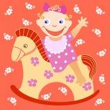 Cheerful kid. Сheerful little girl shaking on wooden horse Stock Photos