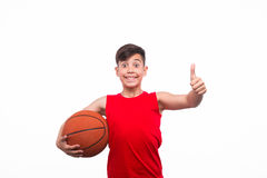 Cheerful kid with basketball. Sportive boy showing thumb up and posing with basketball in hands Stock Image