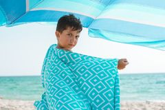 A cheerful kid on the beach wrapped in a bright beach towel. royalty free stock image