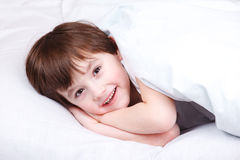 Cheerful kid  in bed Stock Photos