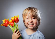 Cheerful kid with a bouquet Royalty Free Stock Photos