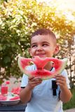 Cheerful kid boy eating a watermelon slice with two heart shape holes royalty free stock image