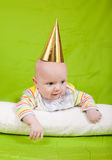 The cheerful kid in a celebratory cap lies on a pillow. Stock Photo