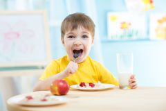 Cheerful kid eating healthy food at home or Stock Images