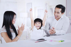 Cheerful kid getting applause from her parents. Photo of excited little girl finishing her homework and get applause from her parents at home stock image