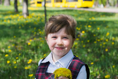 Cheerful kid girl with a bouquet of dandelions Stock Image