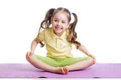 Cheerful kid girl doing exercises on fitness mat Royalty Free Stock Photo