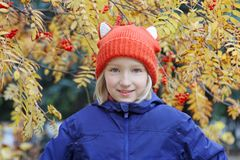 Cheerful kid girl smiling, the child is dressed in a funny knitted warm hat with ears, looks like a fox. Autumn, outdoors portrait. Adorable kid girl smiling Royalty Free Stock Photography