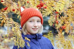 Cheerful kid girl smiling, the child is dressed in a funny knitted warm hat with ears, looks like a fox. Autumn, outdoors portrait. With yellow leaves and rowan Royalty Free Stock Photography