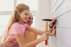 Cheerful kid hammering pin with help of grandfather Royalty Free Stock Image