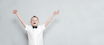 Cheerful kid with hands up. Happy cheerful kid with hands up against the grey wall Royalty Free Stock Images