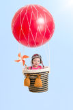 Cheerful kid on hot air balloon in the sky Royalty Free Stock Image