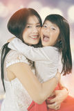 Cheerful kid hugs her mother Stock Photography