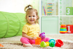 Cheerful kid playing in nursery room Stock Images