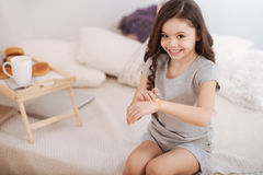 Cheerful kid putting aid bandage on the arm at home Stock Photo
