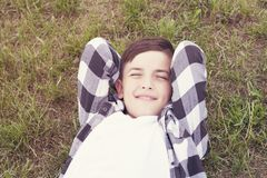 Cheerful kid resting on meadow royalty free stock photography