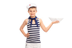 Cheerful kid in a sailor outfit holding a paper boat Stock Photos