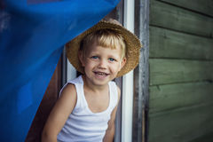 Cheerful kid with straw hat leaning out a window Royalty Free Stock Photo