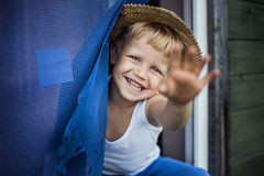 Cheerful kid with straw hat leaning out a window, smiling and waving Royalty Free Stock Photos