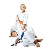 Cheerful kids athletes in kimono doing throws Stock Photo
