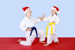 Cheerful kids in caps Santa Claus doing technique karate Royalty Free Stock Photo