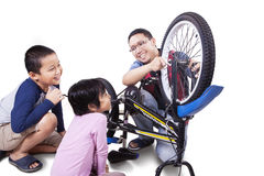 Cheerful kids and dad fixing bicycle Stock Images
