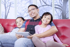 Cheerful kids and dad with tablet smiling at camera Stock Photography