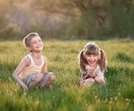 Cheerful kids in the grass. Two cheerful kids sitting in the grass and smiling Stock Photography
