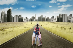 Cheerful kids hugging their father on the road Stock Photo