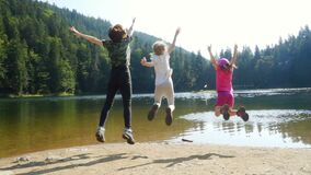 Cheerful kids jumping and enjoying during the summer vacation on a forest lake