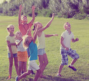 Cheerful kids jumping together in park on summer. Cheerful kids in school age jumping together in park on summer Royalty Free Stock Image
