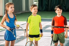 Cheerful kids learning to play tennis. Excited children are listening to trainer with interest. They are standing on tennis court and smiling. Man is showing Royalty Free Stock Photos