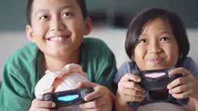 Cheerful kids are playing video games on bed. JAKARTA, Indonesia - June 05, 2018: Two cheerful kids are playing video games while laughing and lying in the stock video footage