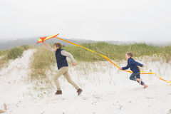 Cheerful kids running with kite at beach Stock Photos