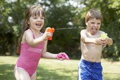 Cheerful Kids Shooting Water Pistols Stock Photography