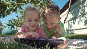 Cheerful kids watching tablet in garden