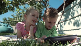 Cheerful kids watching tablet in garden