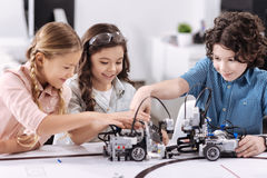 Cheerful kids working on the tech project at school. Delighted from project. Smiling upbeat optimistic children sitting at class and testing robot while working Royalty Free Stock Photography