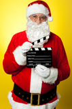 Cheerful Kris Kringle posing with clapperboard. Its time for next shot. Cheerful Kris Kringle posing with clapperboard royalty free stock image