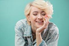 cheerful la bionda felice sta appoggiandosi la sua mano immagine stock