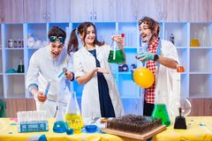 Cheerful lab assistants making experiments. Young funny scientists standing in laboratory and making an experiment Stock Photo