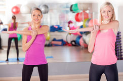 Cheerful ladies are exercising in fitness center Royalty Free Stock Images