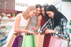 Cheerful ladies are looking down into one bag and putting their hands into it. They are amazed and excited. Cheerful ladies are looking down into one bag and royalty free stock photography