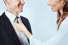 Cheerful lady adjusting necktie of man Royalty Free Stock Photography