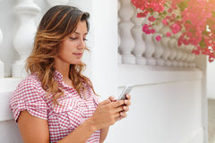 Cheerful lady browsing internet on smart phone Royalty Free Stock Images