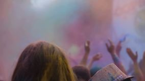 Cheerful lady colored with powder paint dancing and waving hands at Holi fest. Stock footage stock video