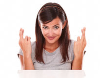 Cheerful lady crossing her fingers while smiling Stock Image