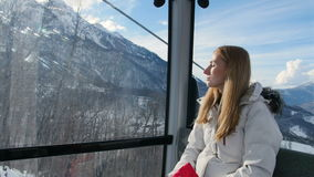 Cheerful lady enjoying the snowy mountain view from the gondola lift. Cheerful lady enjoying the snowy mountain view from the funicular stock video footage