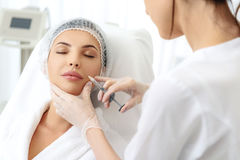 Cheerful lady having rejuvenated injection at clinic Stock Image
